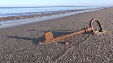 antique rusty metal key on sea resort beach sand