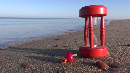 ancient red  hourglass sandglass and rose hips on sea beach