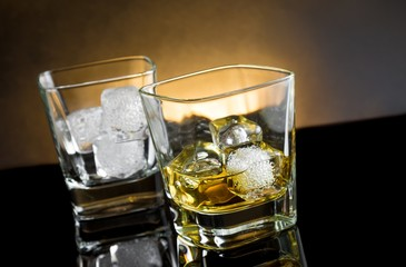 whiskey glasses with ice and warm light on black background