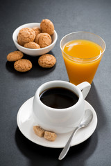 coffee, italian cookies and orange juice on black background