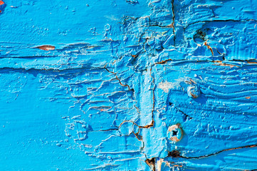 Old wood surface with blue paint flaking and cracking