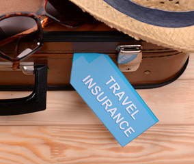 Suitcase and tourist stuff with inscription travel insurance