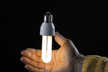 Menschliche Hand, die Energiesparlampe, close-up
