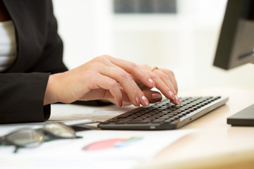 Close-up of businesswoman hands typing documents on keyboard of