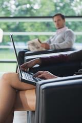 Deutschland, Frau mit Laptop, Mann, die gerade im Hintergrund