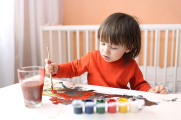 lovely 2 years boy with brush and gouache paints at home