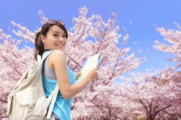 Happy travel woman with sakura tree