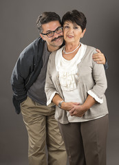 Vertical image of a senior adult woman and her son over gray