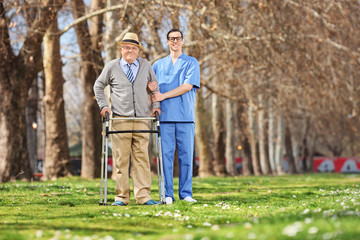 Medical professional and a senior posing in park