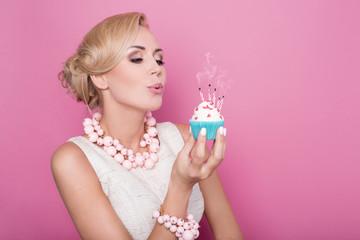 Beautiful women with cream dress holding small cake