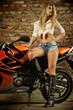 Attraktive blonde junge Frau posiert mit Motorrad
