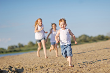 three children playing on beach in summer
