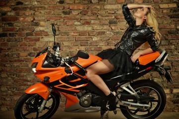 Hübsche junge Frau posiert auf Motorrad