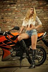 Attraktive blonde junge Frau mit Motorrad