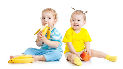 Baby boy and girl eating fruits isolated