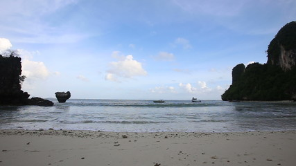 sandy beach with rocks at low tide on the sides of a boat on the