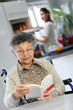 Elderly woman reading book, home helper in background