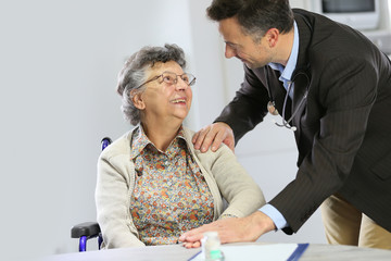 Doctor reassuring elderly woman in wheelchair