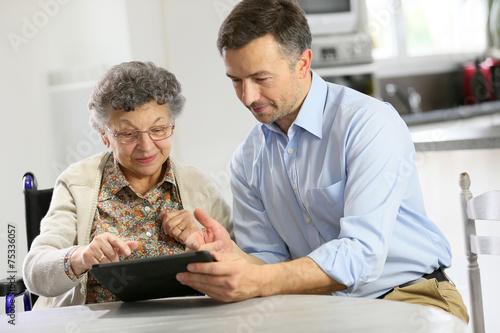 Man with elderly woman using digital tablet - 75336057