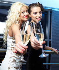 Portrait of elegant young womans with a champagne glasses at cel