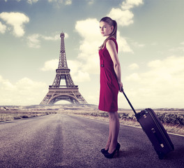 A way to Paris. Young fashionable woman standing with suitcase