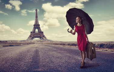 Paris. Eiffel tower. Young business woman hurring with luggage
