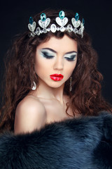 Beauty model woman wearing fur coat, diamond crown. Fashion wint