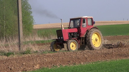 small old agriculture tractor cultivated field in spring