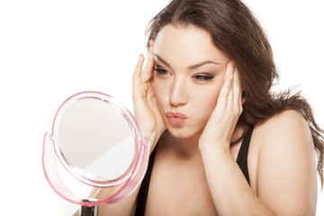 young woman in front of the mirror tightens her face