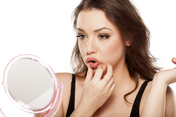 worried young woman in front of the mirror touches her mouth