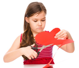 Portrait of a little girl cutting out red heart