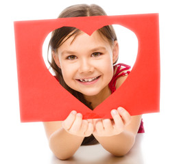 Little girl is looking through heart template