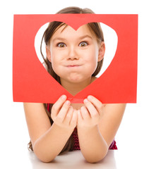 Little girl is looking through heart template