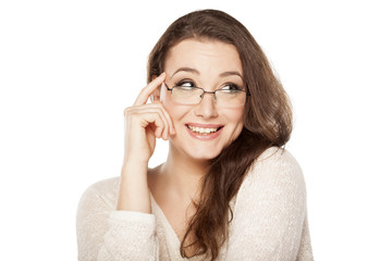 smiling woman with glasses holding a finger on her forehead