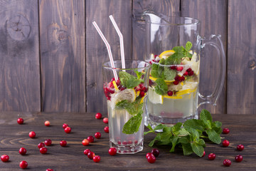 Homemade lemonade with cranberry and mint on a wooden table