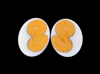 Two halves of an egg with double yolks on black background