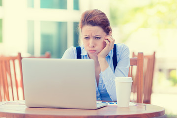displeased worried business woman sitting in front of computer