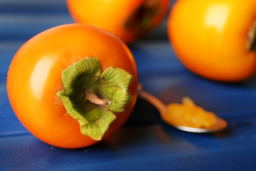 Ripe persimmons on color wooden background