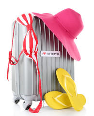 Travel suitcase, hat, swimsuit and flops isolated on white