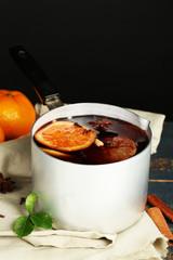 Old metal pan of tasty mulled wine on dark background