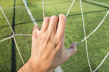 man holding the net of the football goal