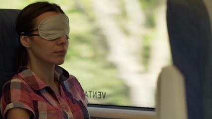 Pretty woman with sleeping eye mask on a train
