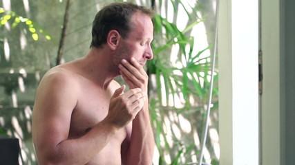 Man applying beauty cream on his face in luxury bathroom