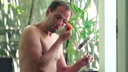 Handsome man applying concealer on his eyelid in bathroom
