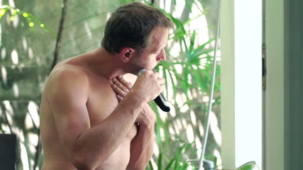 Man shaving beard with electric shaver in bathroom