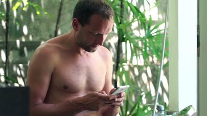 Man texting on smartphone in luxury bathroom