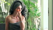 Attractive woman applying concealer on her eyelid in bathroom