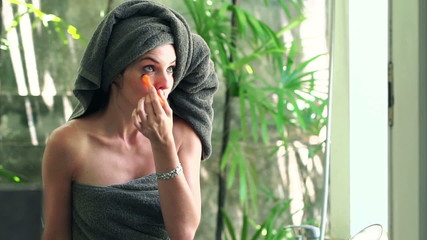 Attractive woman applying concealer on her eyelid in bathroom