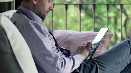 Businessman with tablet computer sitting on sofa at home