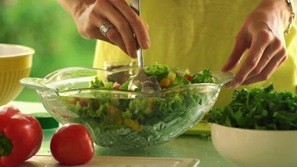 Woman hands mixing salad with spoon in kitchen
